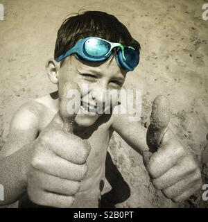 Child's hands on the beach showing thumbs up - Stock Image