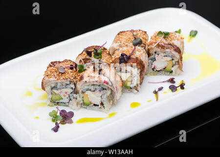 sushi in a plate on a black background, close-up. fish roll - Stock Image