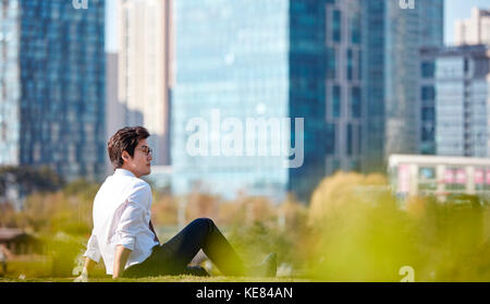 Side view of businessman taking a rest outdoors during daytime - Stock Image