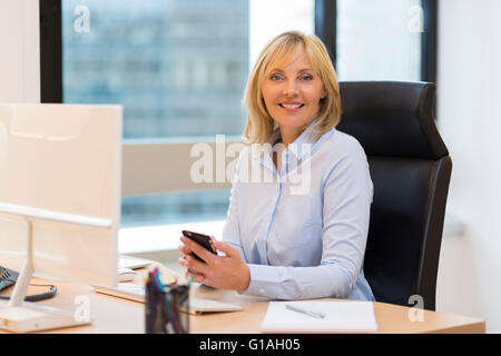 Smiling Middle aged business woman working in modern office. Looking at camera - Stock Image