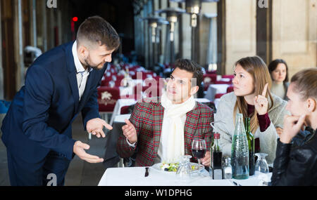 Dissatisfied people expressing displeasure with food and bad service to restaurant manager - Stock Image
