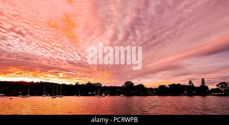 A Pastel Pink colored cloudy sunrise seascape panorama, over sea water with water reflections. Queensland, Australia. - Stock Image