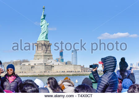 New York city, USA, Statue of Liberty, tourists on a cruise sightseeing the famous place and international landmark - Stock Image