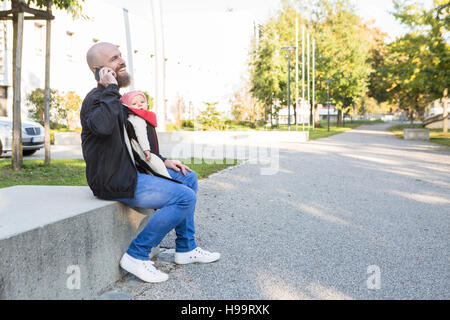 Father with baby girl in baby carrier using phone - Stock Image
