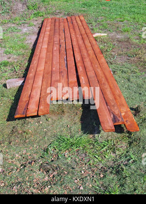 Layer of impregnated wood boards on ground grass - Stock Image