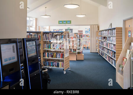 A small village branch library interior with books and electronic withdrawal/return, Wellesbourne, UK. - Stock Image