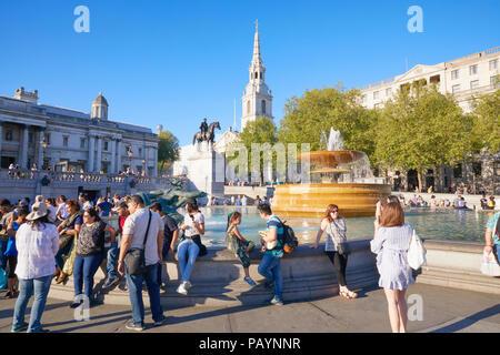 People enjoying sun shine in Trafalgar Square, Whitehall, London, England - Stock Image