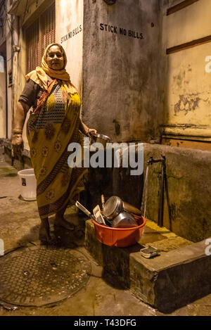 Vertical portrait of a poor lady doing her washing up at a standpipe in Kolkata aka Calcutta, India. - Stock Image