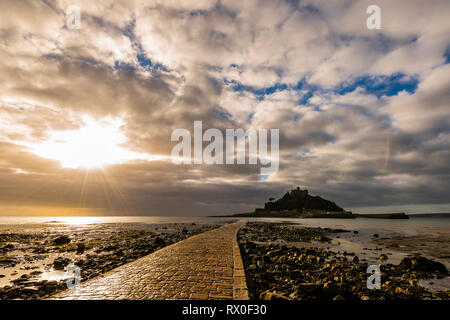 Sunburst over long causeway at St Michael's Mount, Cornwall, UK - Stock Image
