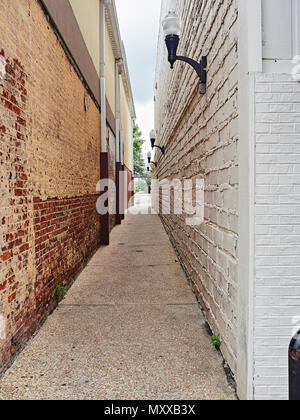 Simple quiet narrow city or urban alley way with high brick walls in Auburn Alabama, USA. - Stock Image