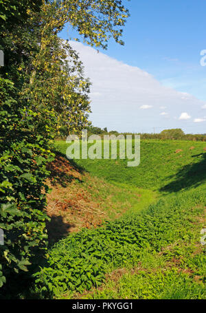 A view of the later defensive ditch and banks surrounding the Norman Bishop's Chapel at North Elmham, Norfolk, England, United Kingdom, Europe. - Stock Image