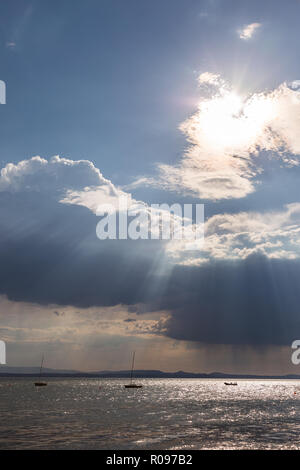 A couple of empty, little sailboat on a lake, beneath a moody sky with sun rays filtering through. - Stock Image