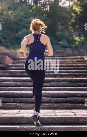 young sporty woman running upstairs in the afternoon on the stairs of the park, morning workout outdoors, sports and healthy lifestyle - Stock Image