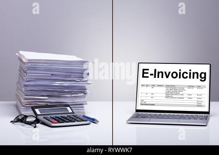 Stacked Of E-invoice Paper And Calculator Is Replace With New Technology Against White Background - Stock Image