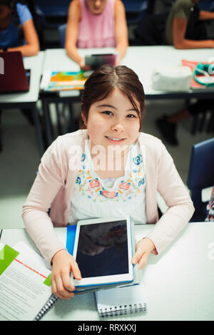 Portrait smiling, confident junior high school girl student using digital tablet in classroom - Stock Image