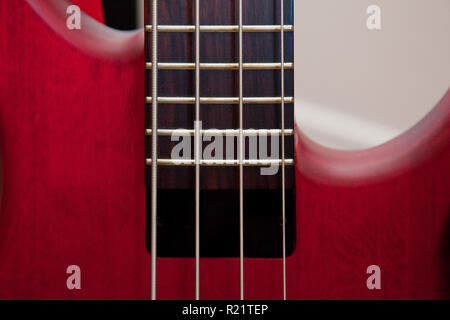 Bass guitar strings and frets on a beautiful red instrument - Stock Image