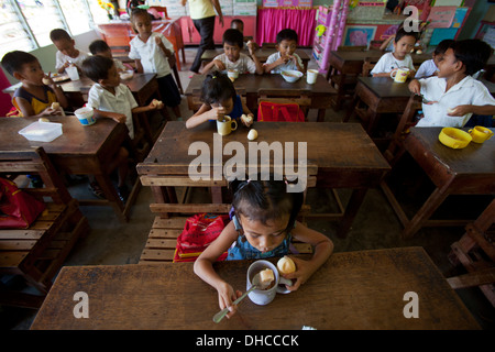 Children enjoy a free lunch during a feeding program event at Wasig Elementary School in Wasig, Oriental Mindoro, Philippines - Stock Image