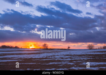 Sunset with orange sun in the clouds over snowy rural fields - Stock Image