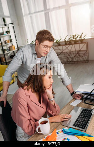 handsome man standing near tired girlfriend sitting and looking at laptop - Stock Image
