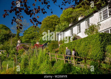 UK, Cumbria, Hawkshead, Far Sawrey, walkers on footpath to B5285 road through village - Stock Image
