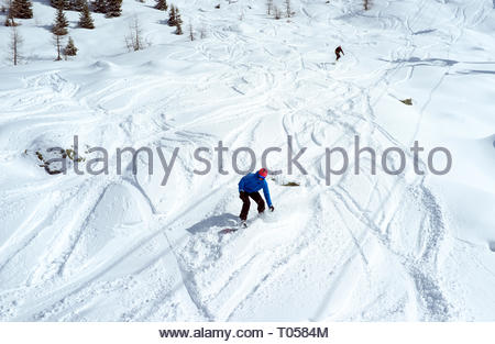 Two snowboarders go off piste, at the ski resort in Sainte-Foy-Tarentaise, Auvergne-Rhône-Alpes region in south-eastern France. - Stock Image