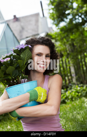 portrait of young woman holding flowerpot - Stock Image