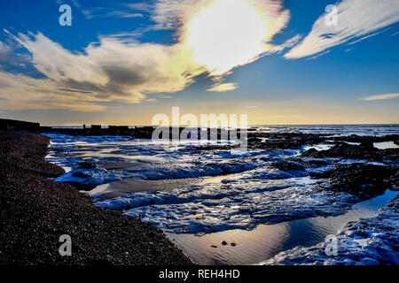 Beautiful rock pools next to a pebble beach behind is the sea and a clear sky with white clouds, the sun is low in the sky back lighting the rock pool - Stock Image