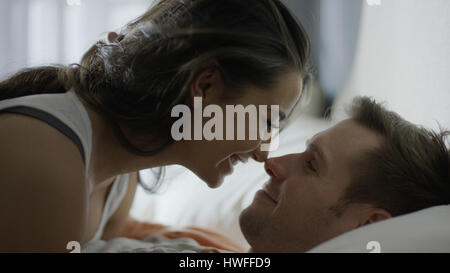 Close up profile of smiling happy couple touching noses on bed - Stock Image