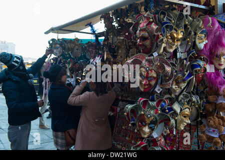 Venice, Italy. 25th Feb, 2014. Tourists try on carnivale masks at a stall near the Rialto Bridge and Grand Canal, VeniceVenice Carnivale Credit:  MeonStock/Alamy Live News - Stock Image