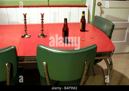 Beer bottles, candlestick holders and coins on empty kitchen table - Stock Image