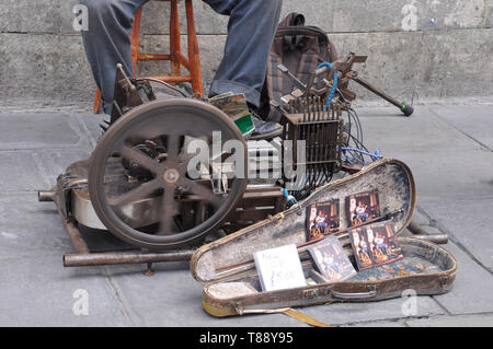 Mechanical Guitar accompanying its constructor who is busking on the street in Bath Somerset, - Stock Image