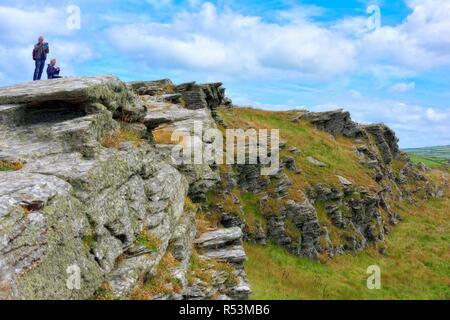 Tourists standing on a cliff edge,Tintagel Peninsula, Cornwall,England,UK - Stock Image