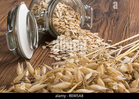 Rolled oats and dry ears on wood table. Common oat. Avena sativa. Beautiful close-up of a lying glass jar. Spilled flakes, dry cereal spikes, grains. - Stock Image