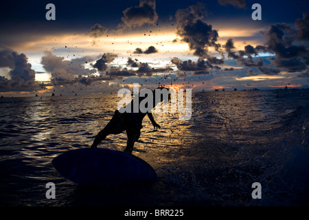 A skim boarder carves through a breaking wave at sunset on Long Beach in Boracay, Philippines. - Stock Image