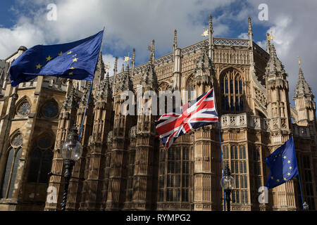 On the day that MPs in Parliament vote on a possible delay on Article 50 on EU Brexit negotiations by Prime Minister Theresa May, the EU flag and the British Union Jack fly in front of Westminster Abbey during a Brexit protest opposite Parliament, on 14th March 2019, in Westminster, London, England. - Stock Image