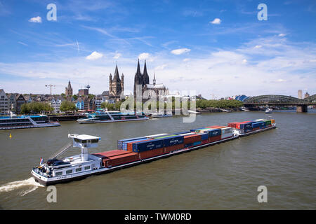 container ship on the river Rhine at the old part of the town with the romanesque church Gross St. Martin and the cathedral, Cologne, Germany.  Conati - Stock Image