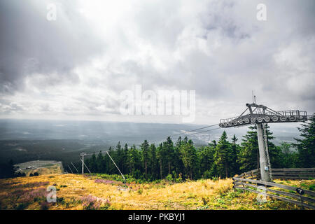 Mountain lift in the summer with a view over a valley in cloudy weather - Stock Image