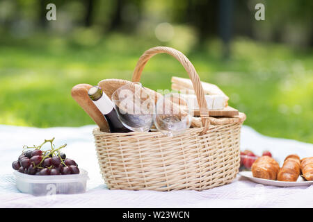 picnic basket, food and wine at summer park - Stock Image