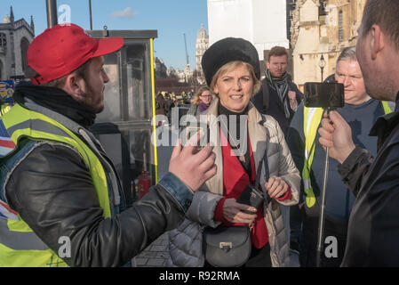 London, UK. 19th Dec, 2018. MP Anna Soubry was recognised on the pavement outside Parliament by extrem Brexiteers who were protesting they and chased and hassled along the pavement, asking why she was calling for a second referndum. She answered one who she called 'Michael' as she hurried to escape and then called police for assistance after another man shouted at her 'You fucking traitor!' complaining that this was an offence. Police quickly escorted her away from the group. Credit: Peter Marshall/Alamy Live News - Stock Image