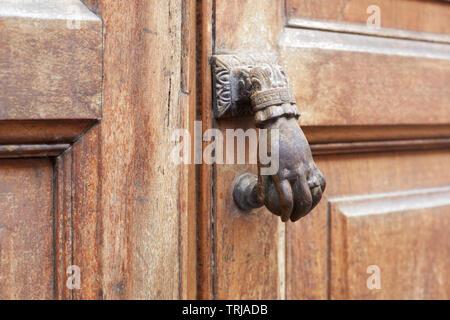 Old door knocker in shape of hand and wooden door background - Stock Image