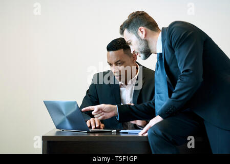 Businessmen discussing project on laptop - Stock Image