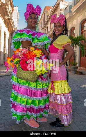 Cuban women with traditional floral  clothing posing for tourists in street in  Old Havana, Cuba - Stock Image