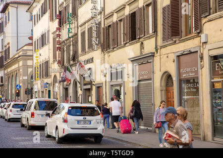 Street scene in Florence city centre with people walking and parked cars,Tuscany,Italy - Stock Image