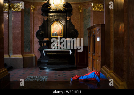 A pilgrim sleeps in a sleeping bag on the floor of the basilica in the Sanctuary of Jasna Góra, Poland 2018. - Stock Image
