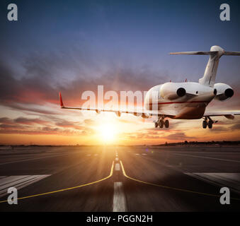 Private jet plane landing on runway in beautiful sunset light. Modern and fastest mode of transportation, business and succesfull style of life. - Stock Image