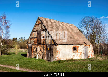 Derelict old barn building with stone exterior and half timbered tudor-style facade on Gutshaus Manor House estate, Friedenfelde,Gerswalde,Brandenburg - Stock Image