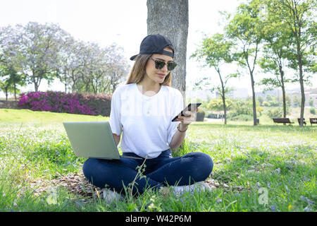 Front view of a happy student girl working with a laptop and smartphone in a green park of an university campus - Stock Image