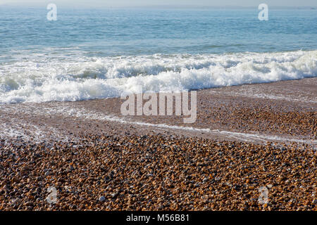 Waves crashing onto a pebble beach - Stock Image