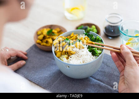 Curry chicken, broccoli and rice, woman with chopsticks - Stock Image