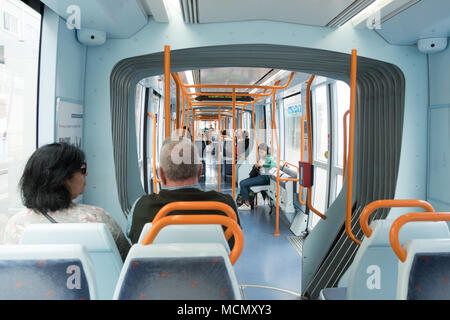 Santa Cruz de Tenerife; an old Spanish colonial-style building undergoes renovation behind a screen as a tram takes passengers through the town. - Stock Image